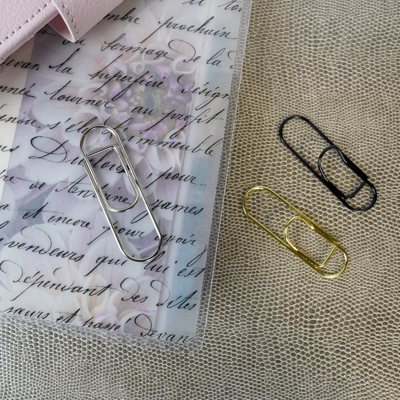 Metal Pen Clips in black, gold, and silver on a French Handwriting cover from Jane&