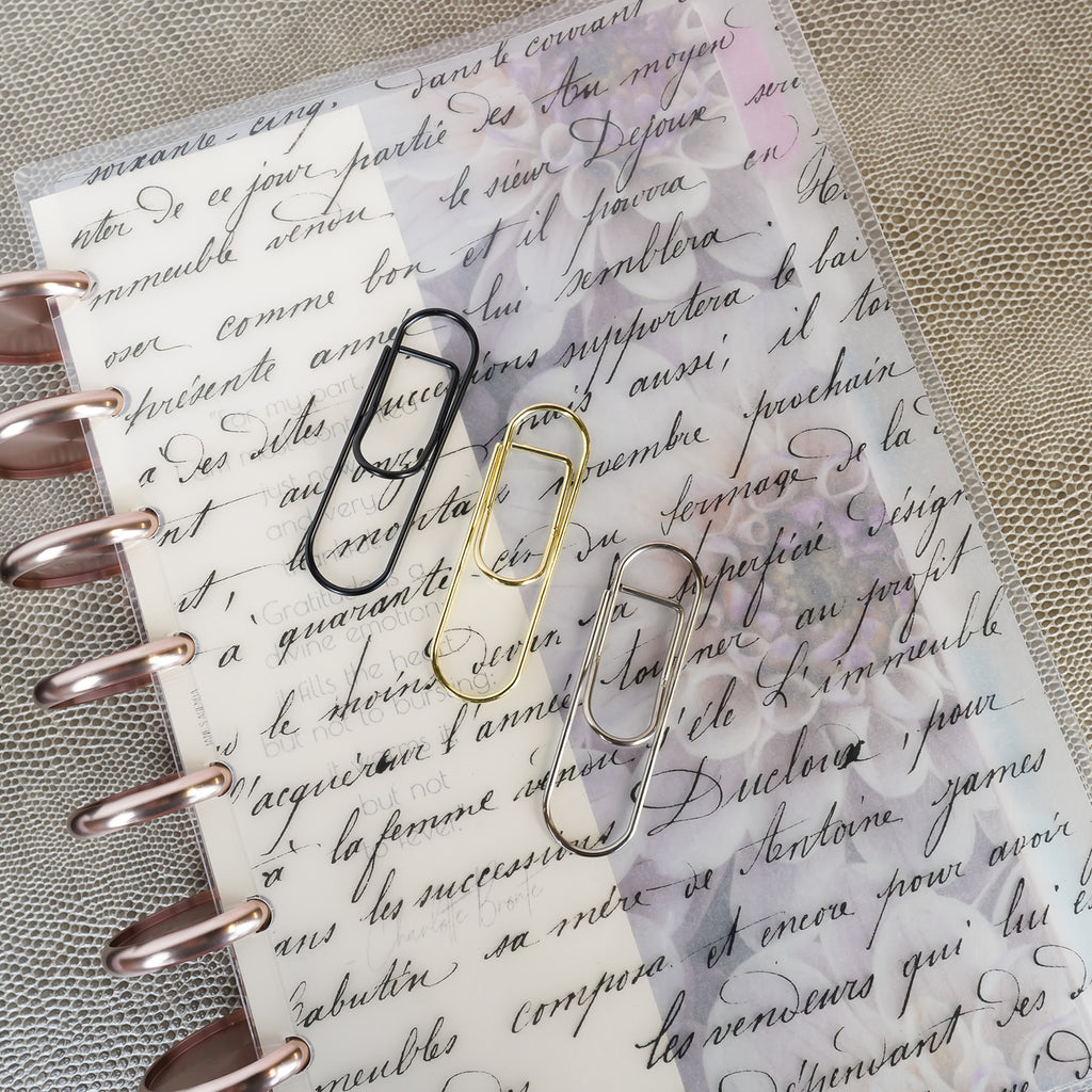 Metal Pen Clips in black, gold, and silver from Jane's Agenda® on a discbound planner with a French Handwriting Cover.