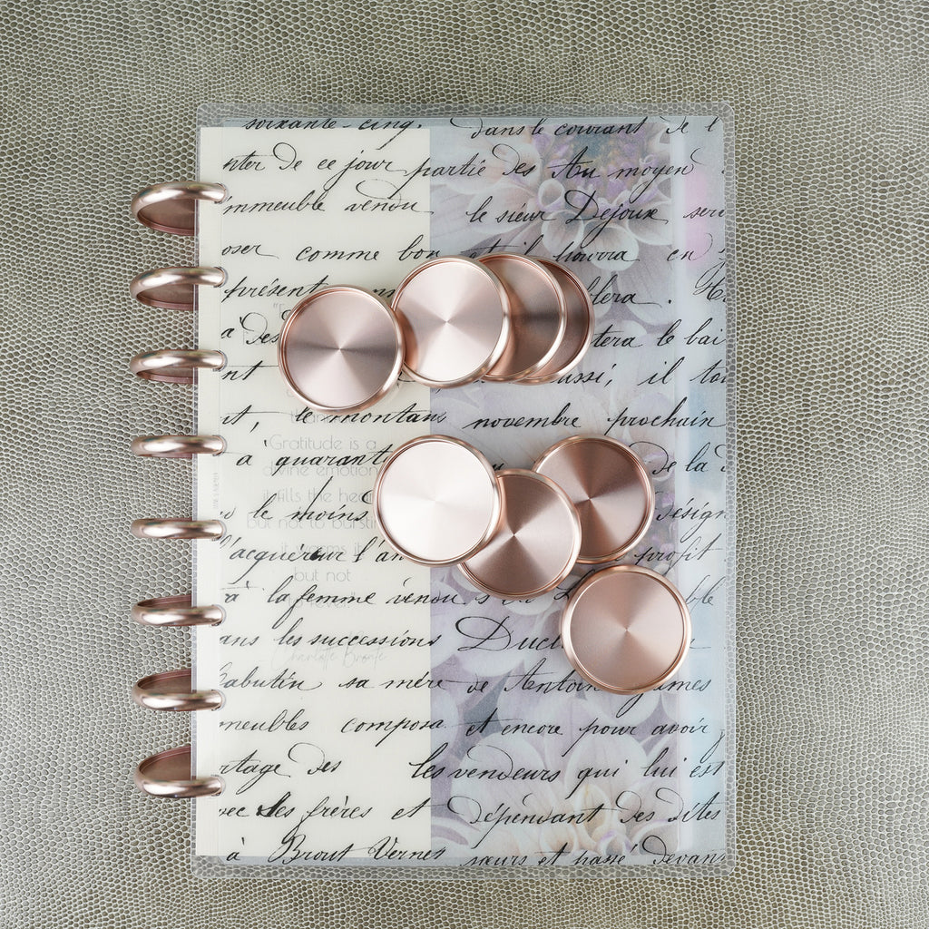 1.5 inch Aluminum Rose Gold Binding Discs displayed on a Jane's Agenda® French Handwriting Discbound Planner Cover.