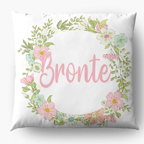 White cushion with a ring of pastel coloured flowers personalised with a name in light pink