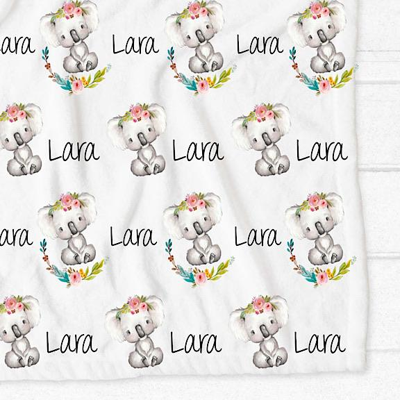 Minky fleece pram cot single bed blanket with white background and grey and white koalas wearing a floral crown sitting in a floral wreath personalised with the name Lara