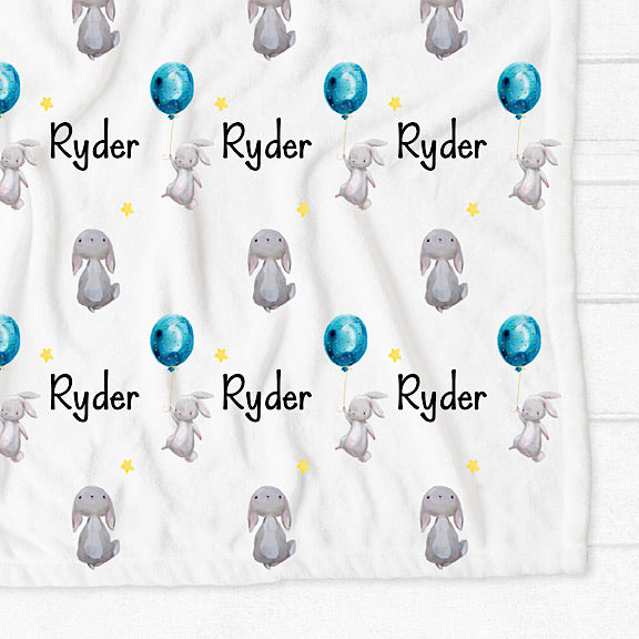 Personalised easter bunny fleece minky blanket with a white bunny tiptoeing holding onto a blue balloon and a white bunny looking up at the yellow stars