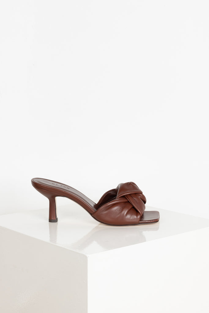 The Lana Mules by By Far are squared toe mules in a soft and supple dark brown leather with a curved heel and a large knot