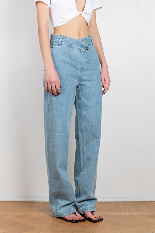The Madras Jeans by Gauge81 is a high waisted denim with a cross-over button and a straight leg cut in a light blue wash