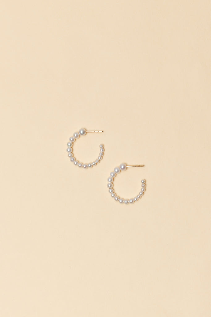 The Boucle Marco Earrings by Sophie Bille Brahe are 14Kt Gold hoop earrings with freshwater pearls descending in size from the front to the back