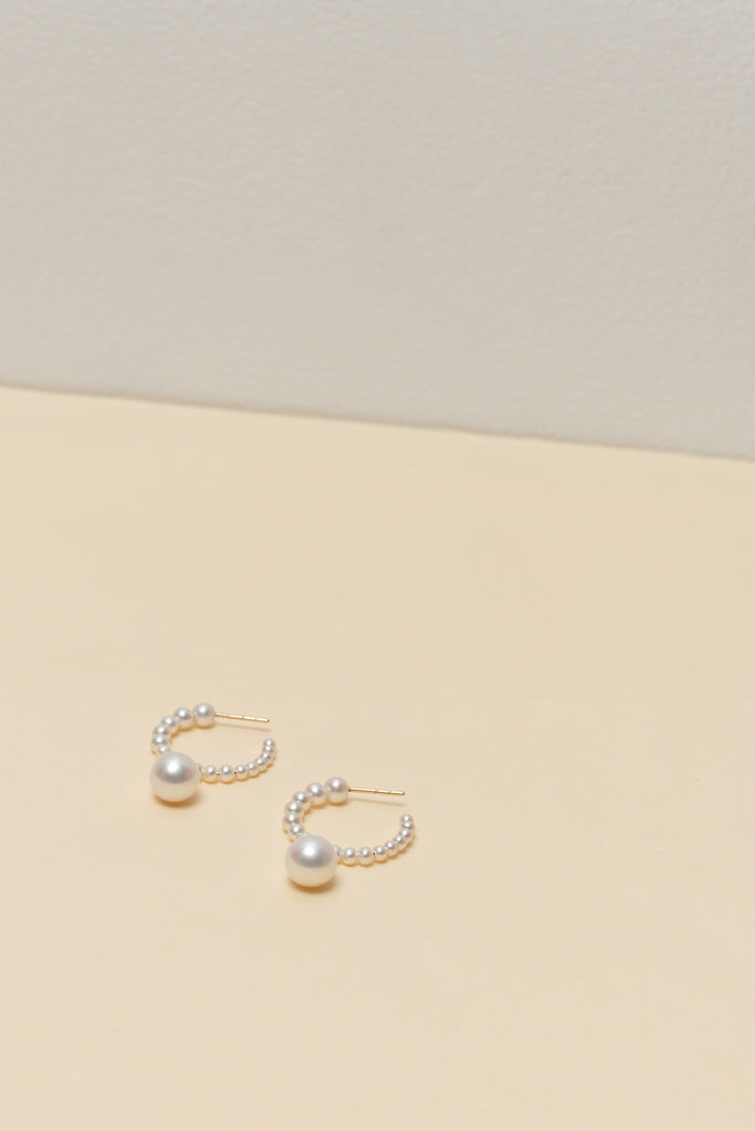 The Boucle Marco Perle Earrings by Sophie Bille Brahe are 14Kt Gold hoop earrings with freshwater pearls descending in size from the front to the back