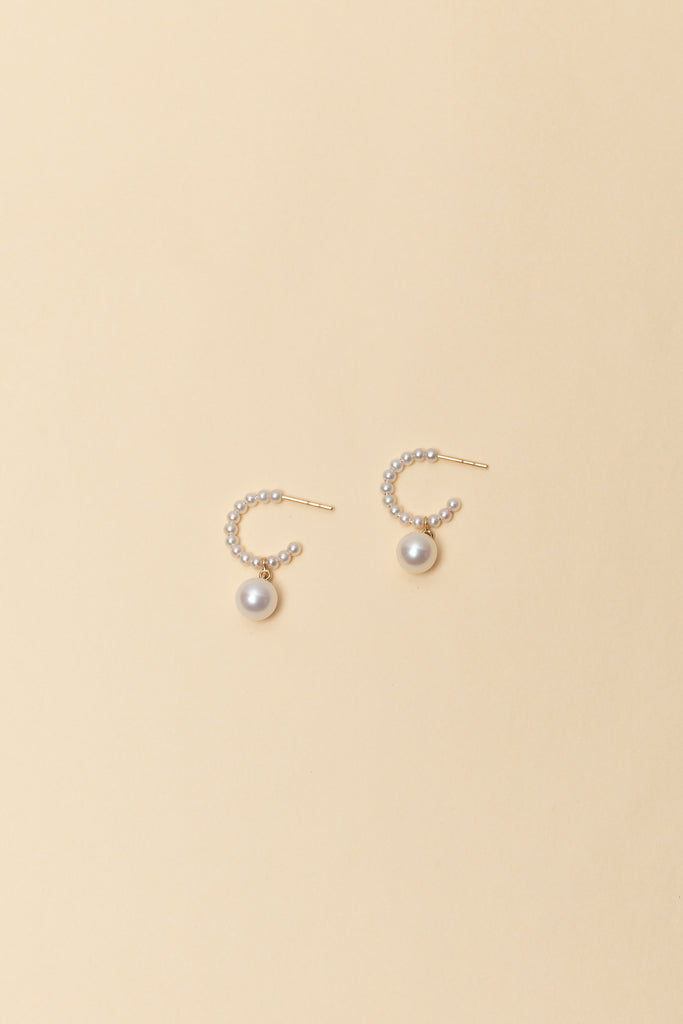 The Marco Perle Earrings by Sophie Bille Brahe are small 14Kt Gold hoop earrings with freshwater pearls and a single pendant pearl