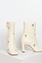 The Isa Boots by Wandler are high shaft boots with a squared toe silhouette in cream with golden eyelets