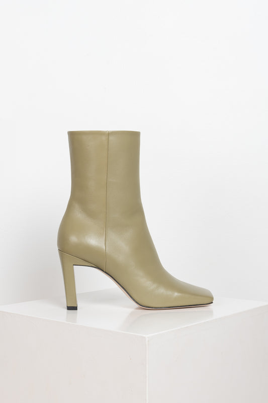 The Isa Boots by Wandler are high shaft boots with a squared toe silhouette in a faded green color