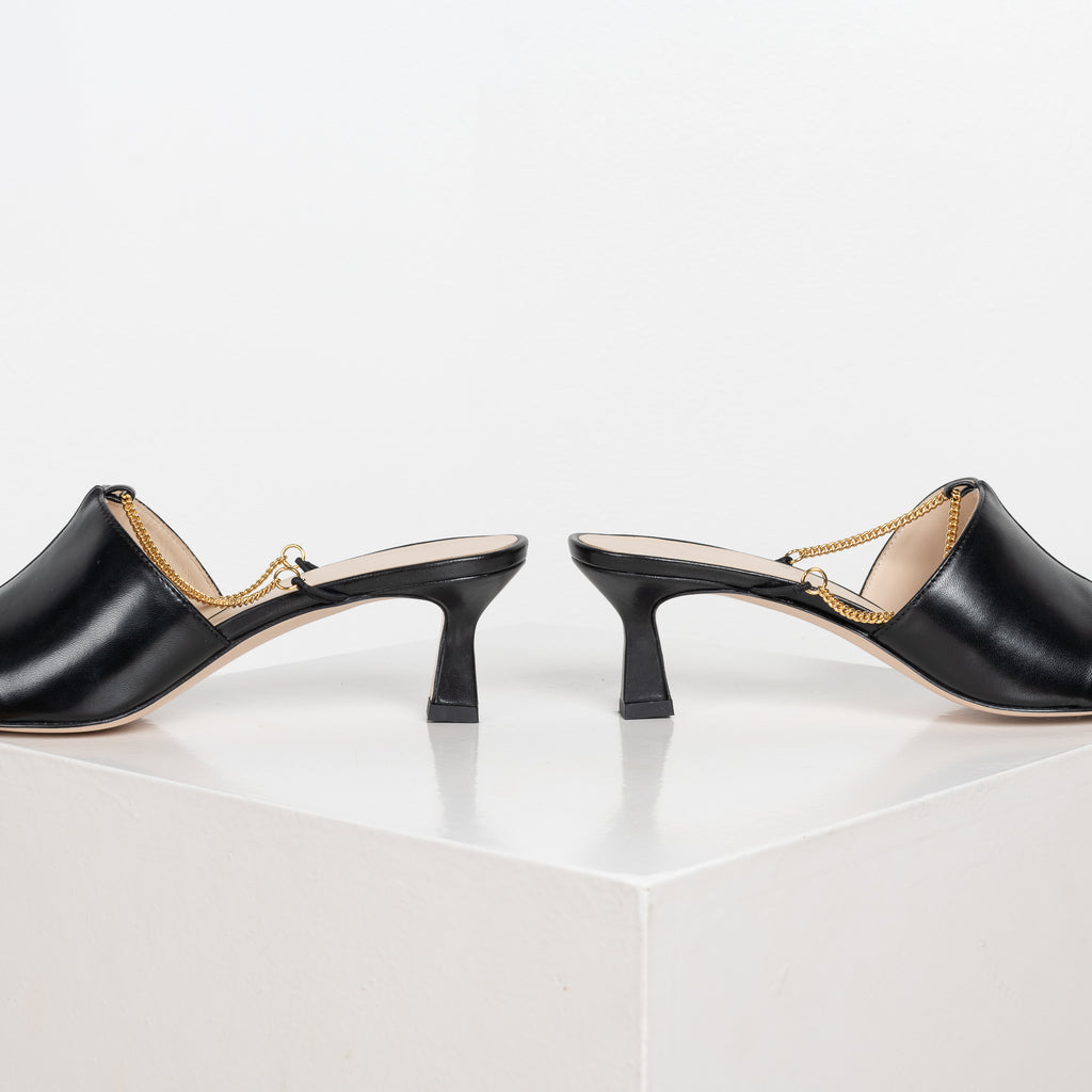 The Isa Chain Mules by Wandler are kitten heel mules with a squared toe silhouette and a feminine chain detail