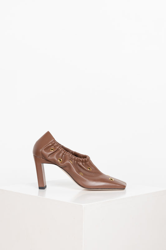 The Mia Mules by Wandler are block heel mules with soft voluminous pleats around the shoe and golden eyelets