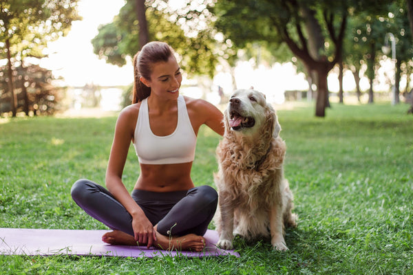 woman fighting off stress symptoms outdoors with dog