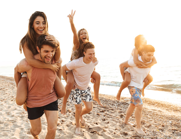 happy young people laughing on a beach