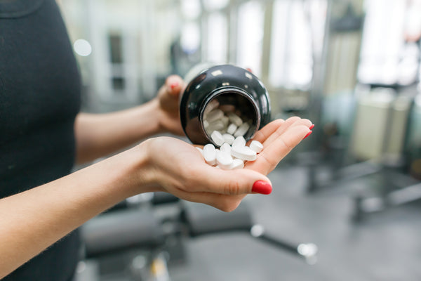 Woman taking supplements for low testosterone in gym
