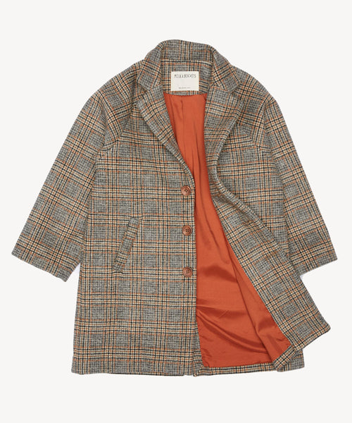 Unisex Prince Charles check wool coat in warm tones, with raglan sleeves, and a  generous fit to allow for cosy layering underneath.  milk and biscuits available in  ireland