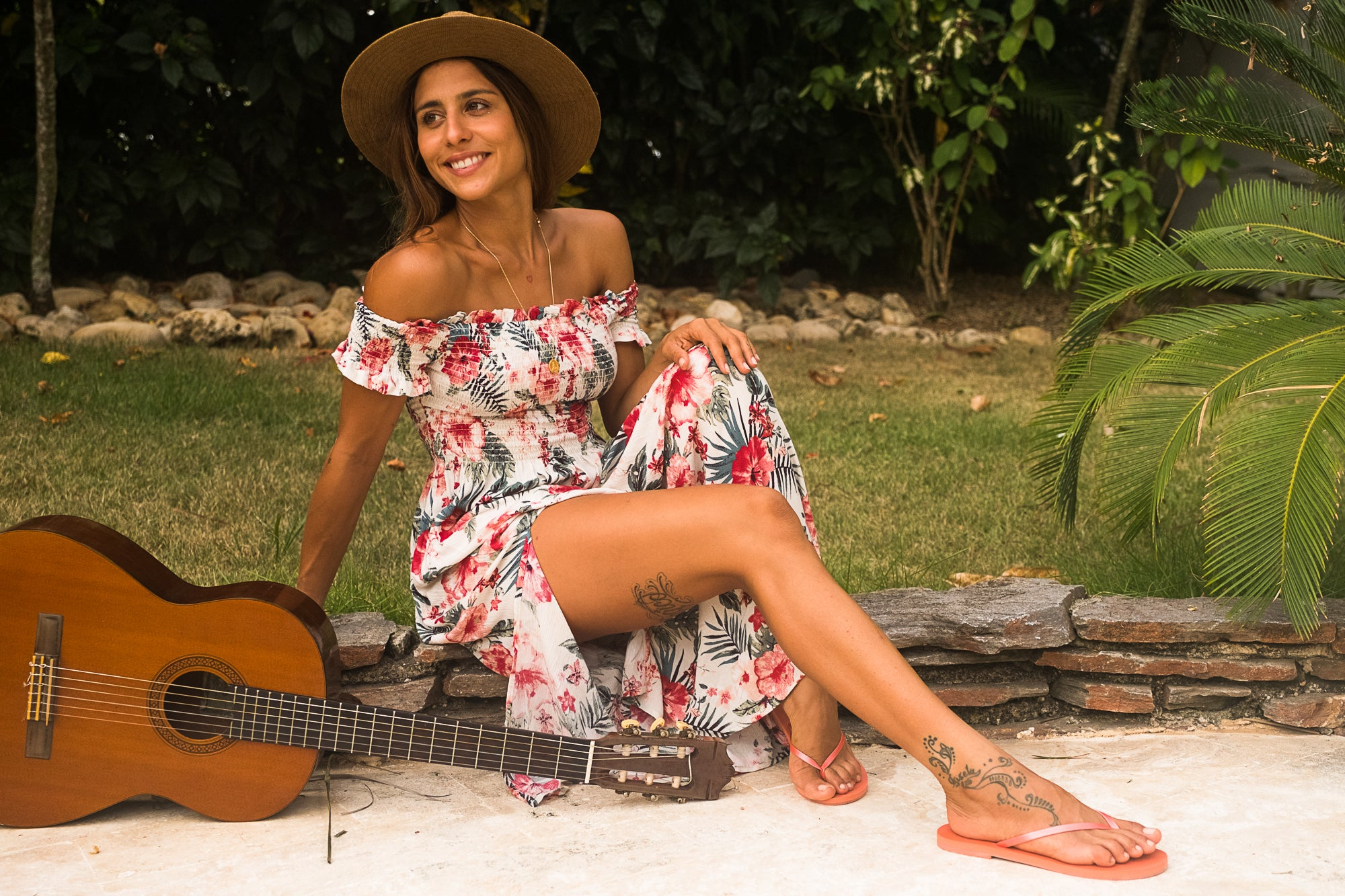 Woman posing next to guitar wearing Koy Resort floral dress and Malvados sandals
