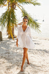 Beautiful brunette model walking on Miami Beach. Model wearing white bikini coverup with lace trim and ruching at bust to flatter figure.