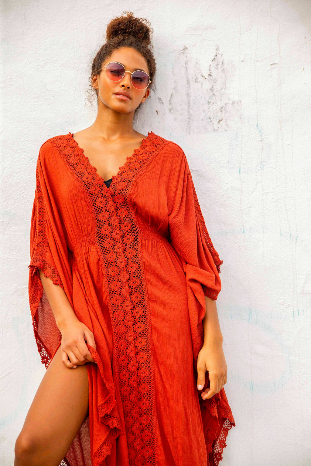 Beautiful black model wearing long terra cotta coloured bikini and swim suit coverup. Coverup has lace trim down center and on hem.
