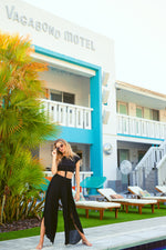 Blonde model standing in front of Vagabond Motel in Miami Florida. Model posing and wearing black sheer slit pants.
