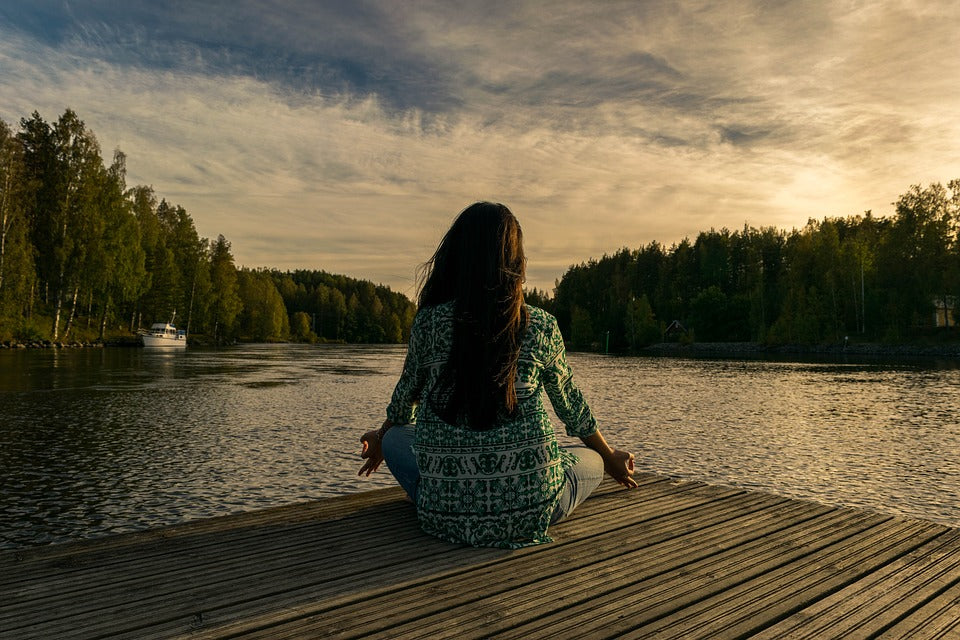 A woman sitting down meditating near a lake at twilight.
