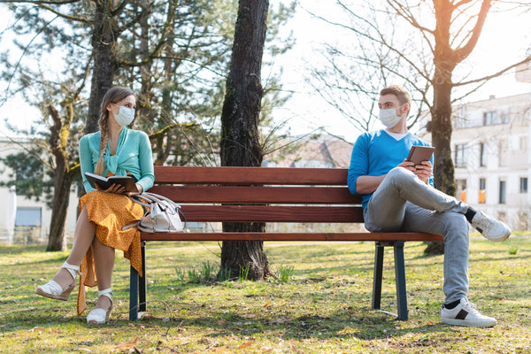 Man and woman sitting on a bench with facial masks