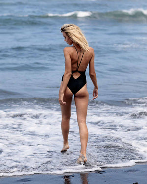 Solar Eclipse black elegant one piece swimsuit. High neck with subtle twist detail at low back. Mid rise. Front view.