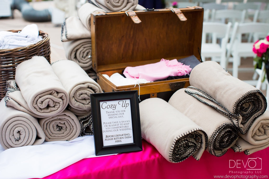Tan fleece blankets paired with shawls for guests at an unseasonably chilly summer wedding. Credit: Devo Photography