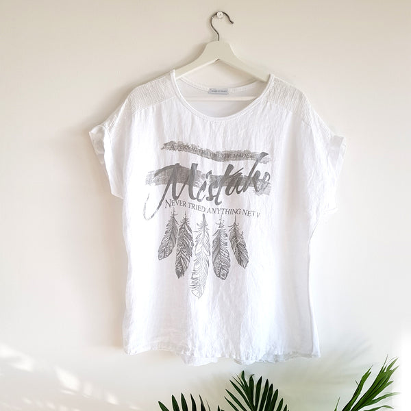 A person who never made a mistake, never tried anything new slogan t-shirt with feather motif