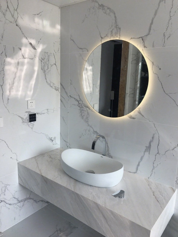 Marble vanity with lights around the mirror