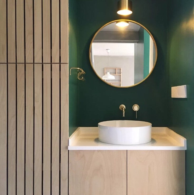 teak modern vanity with green wall
