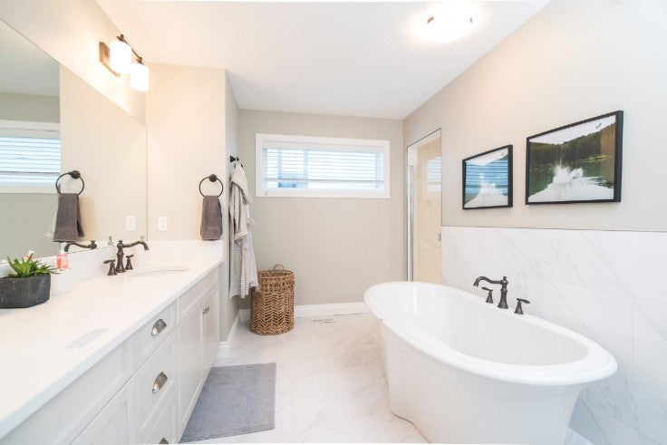 white vanity and tub with bridge faucets