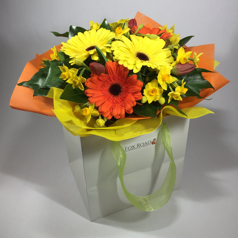 Bright flower gift bag filled with yellow and orange gerberas