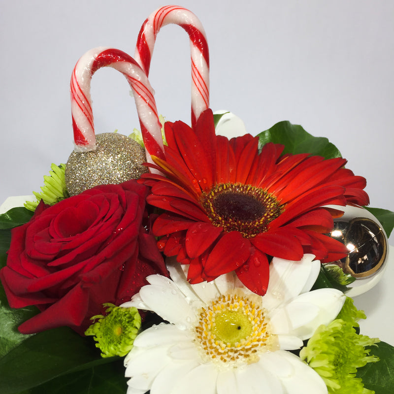 Candy canes and baubles with Christmas flowers