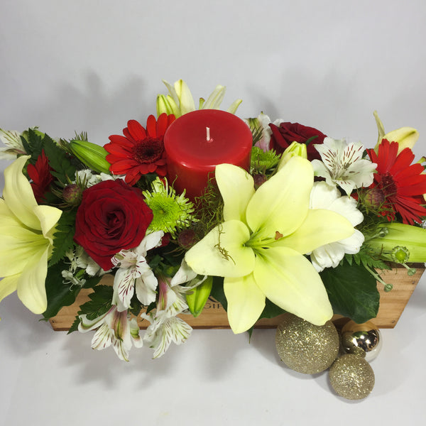 Lilies, roses and Christmas baubles in a wooden gift box
