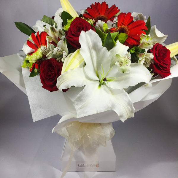 Bright lilies and red gerberas in a cardboard vase
