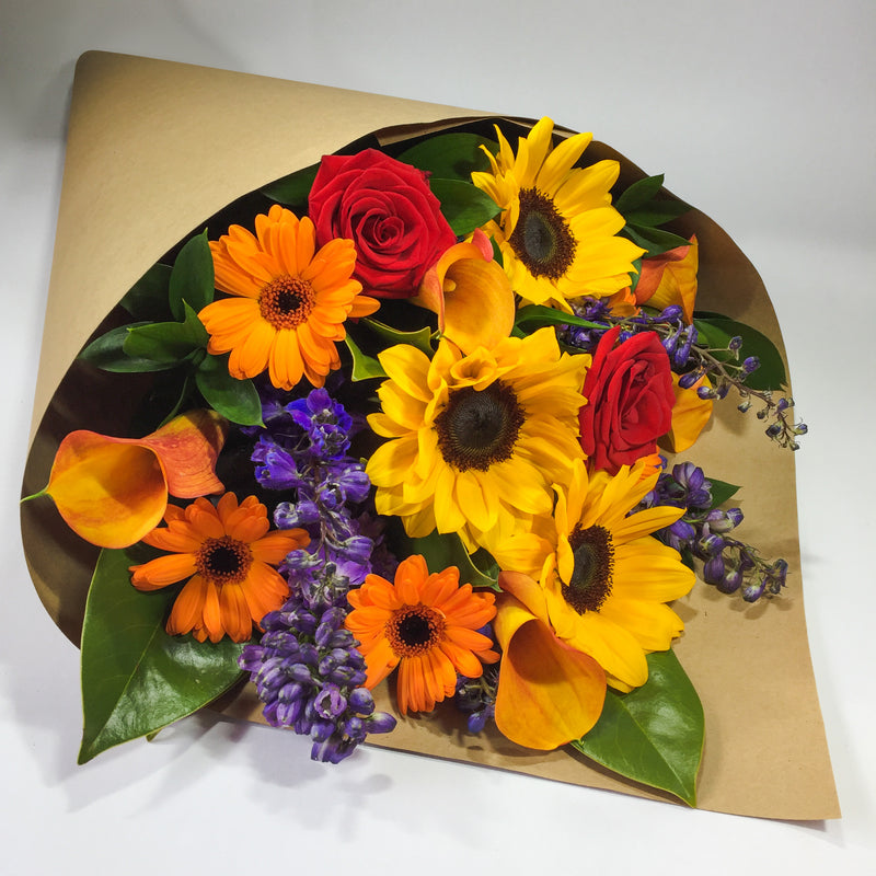 Bright sunflowers and red roses presented in a wrap