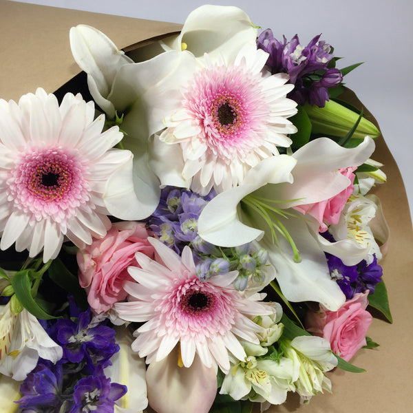 Close up of flower arrangement filled with gerberas and lilies