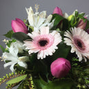 Close up of Gerberas, roses and fresh greenery in a vase