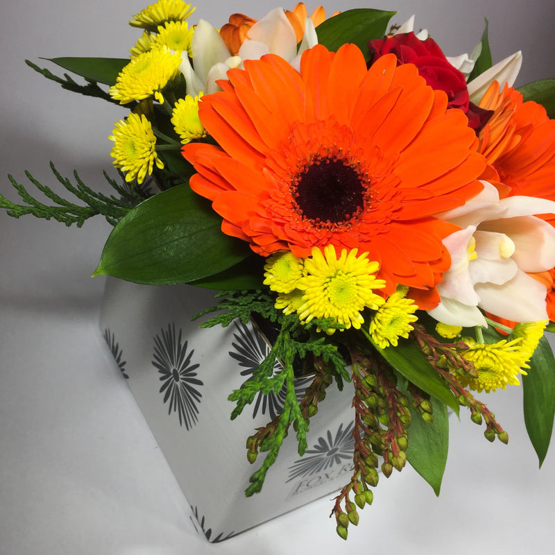 Bright flowers in a birthday box with greenery