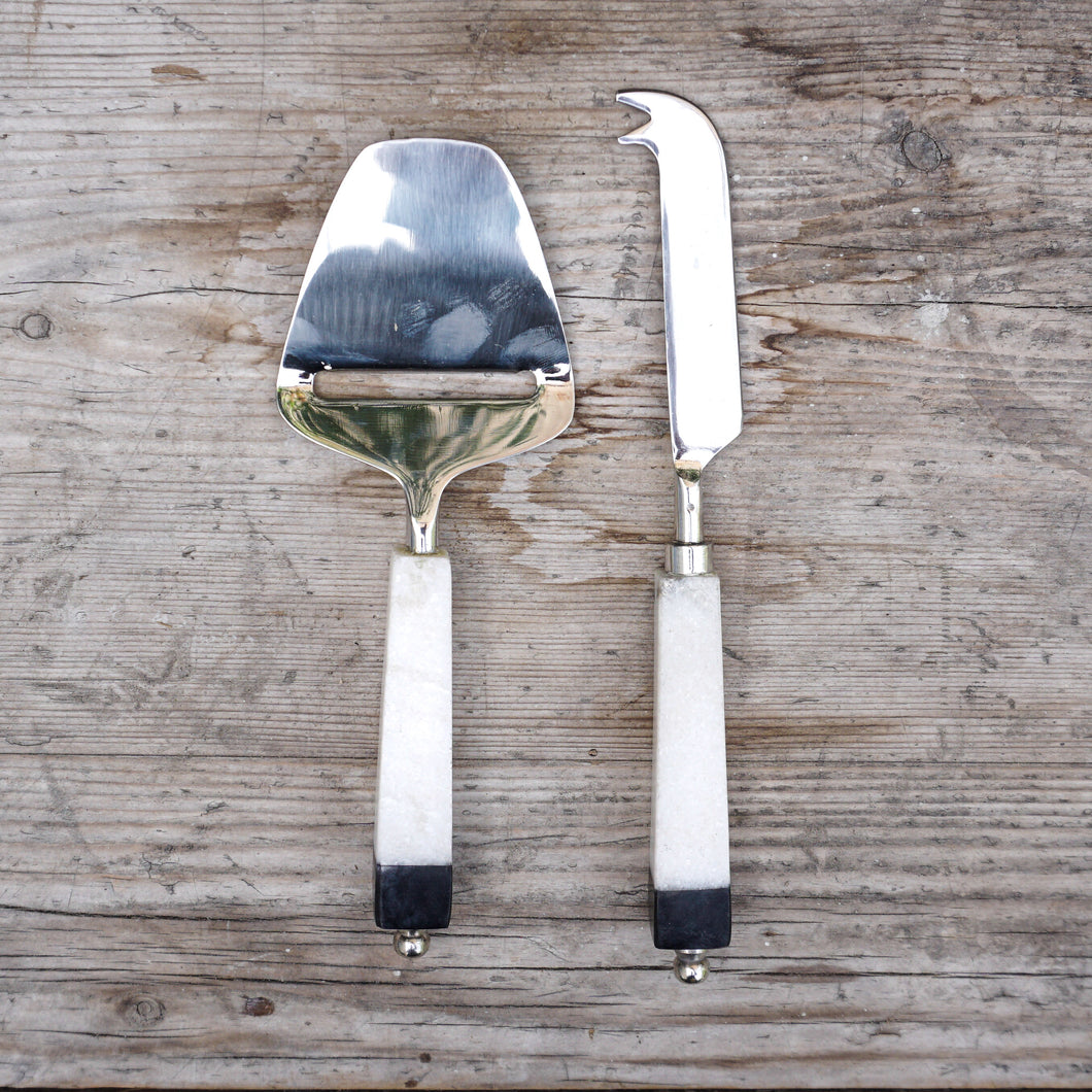 Set includes one cheese knife and one cheese plane made of stainless steel with white marble handles tipped in black at the ends