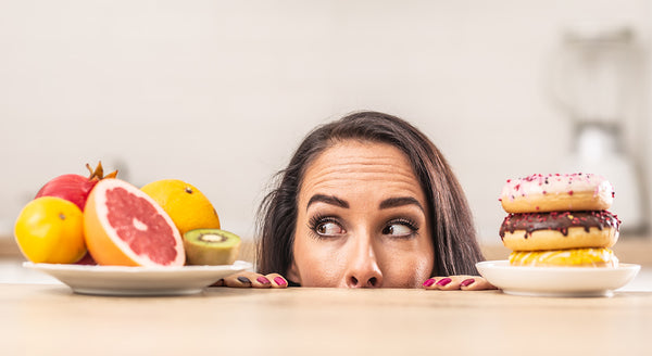 Women trying to choose between healthy fruits or donuts