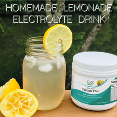 Mason jar glass filled with lemonade, next to a small tub of Ionic-Fizz Calcium Plus supplement and fresh squeezed lemons.