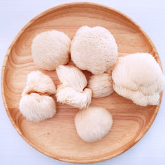 Fluffs of Lion's Mane mushrooms displayed on wooden tray