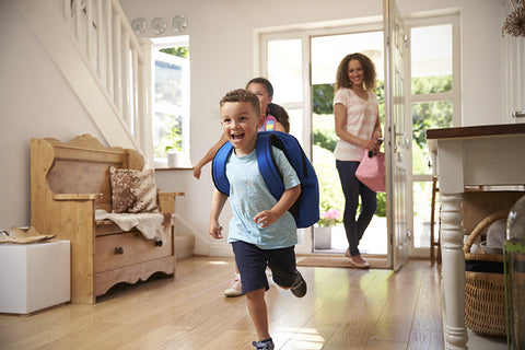 Boy and girl are happy running into the house after school, as mom holds the door open.