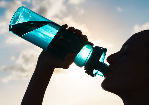 silhouette of a person drinking fluids from see-through water bottle