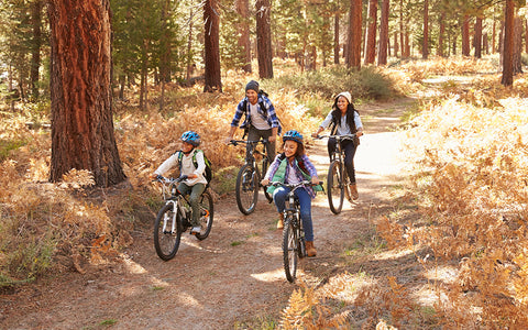 family of 4 enjoying a bike ride on a dusty forest trail