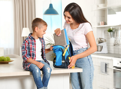 Mom and son unpack his school backpack and talk about his day.