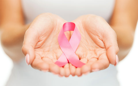 close up of hands holding a pink awareness ribbon for Breast Cancer Awareness
