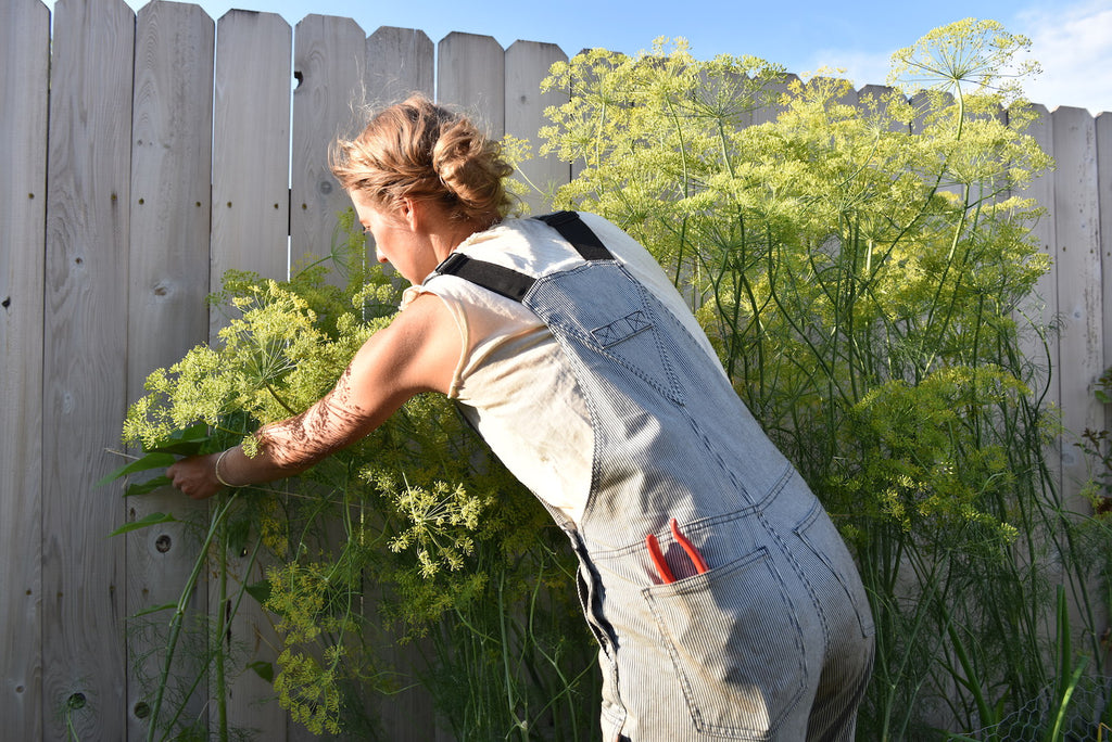 Nicole Freshley tying up a plant in front of a wooden fence, wearing the Freshley Overall in indigo stripe denim