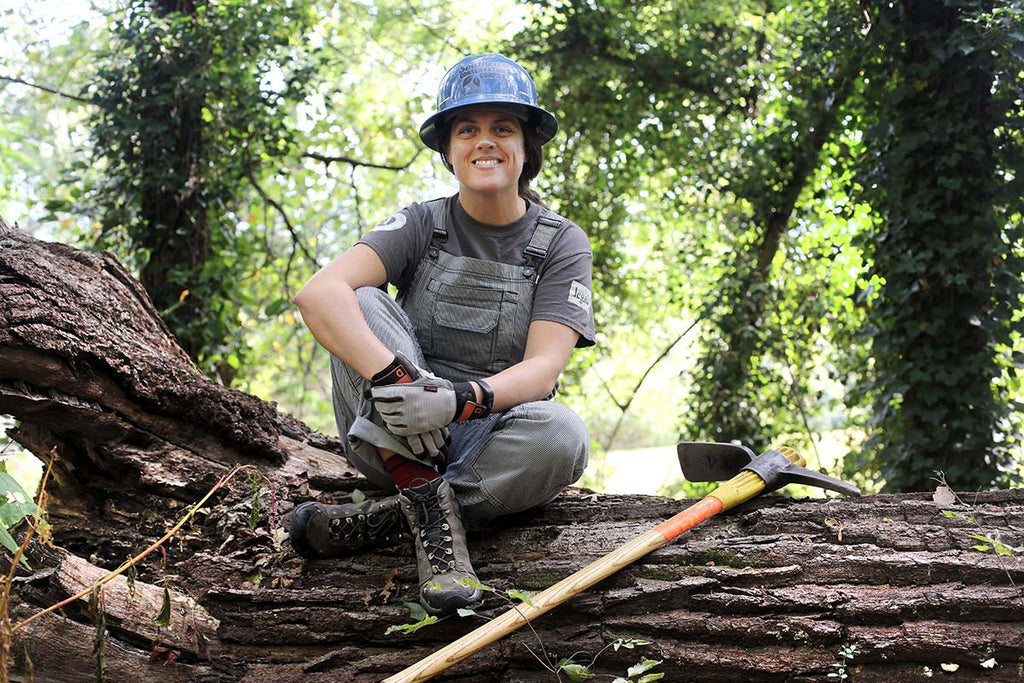 Brenna Kelly on a fallen log wearing the Dovetail Workwear pinstripe overalls for women, multi-purpose gloves and a tee shirt. Brenna is the director of the Southeast Conservation Corps, part of Conservation Legacy